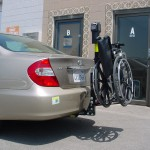 TRILIFT Ultra Lite carrying a manual wheelchair on a Toyota Camry.